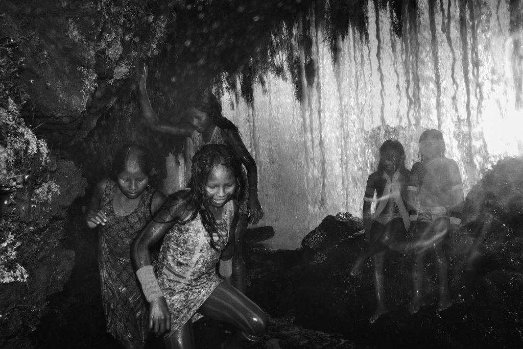 Territoire indigène de Kayapó, Pará. Des enfants Kayapó jouent derrière une chute d'eau dans le village Kuben-Kran Ken. Le territoire Kayapó est la plus grande zone protégée tropicale au monde, plus de 3,2 millions hectares de forêts et de broussailles abritant de nombreuses espèces menacées. Il constitue une barrière majeure à la déforestation qui progresse depuis le sud. Kayapó Indigenous Territory, Pará. Kayapó children play behind a waterfall in the Kuben-Kran Ken village, in the southern Pará State. The Kayapó's territory is the largest tropical protected area in the world, more than 3.2 million hectares of forest and scrubland containing many endangered species. It serves as a crucial barrier to deforestation advancing from the south.
